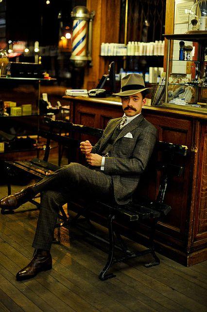 Tan fedora w/ black hatband, dark brown oxfords, dark 'stache, grey 3-pc. suit; classic barbershop complete w/ red & blue spiral-striped pole, wood & cast-iron bench