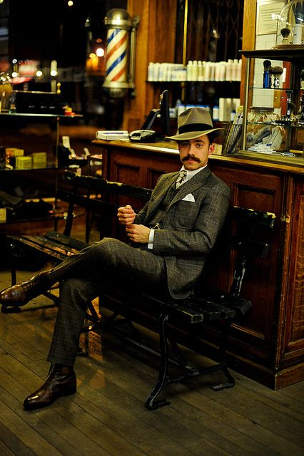 Tan fedora w/ black hatband, dark brown oxfords, dark 'stache, grey 3-pc. suit; classic barbershop complete w/ red & blue spiral-striped pole, wood & cast-iron bench