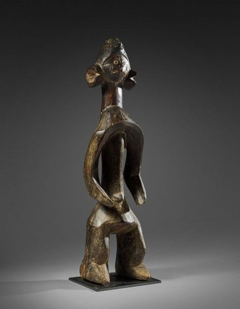 Eve Auction 12/12/16 Est.  8-12 000 € Statue MUMUYE - Nigéria Bois à patine brun foncé - Résine - Graines d'abrus - Cauris Hauteur: 69 cm Personnage dont les bras enveloppent un torse fin. La partie inférieure est lourde. L'ensemble est surmonté d'une petite tête au visage très expressif recouvert de scarifications rituelles. Les oreilles sont importantes et en relief.