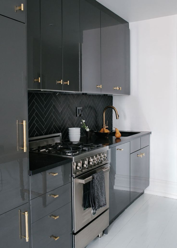 Glossy Ikea cabinetry is accented by bronze hardware and a honed-marble herringbone backsplash.