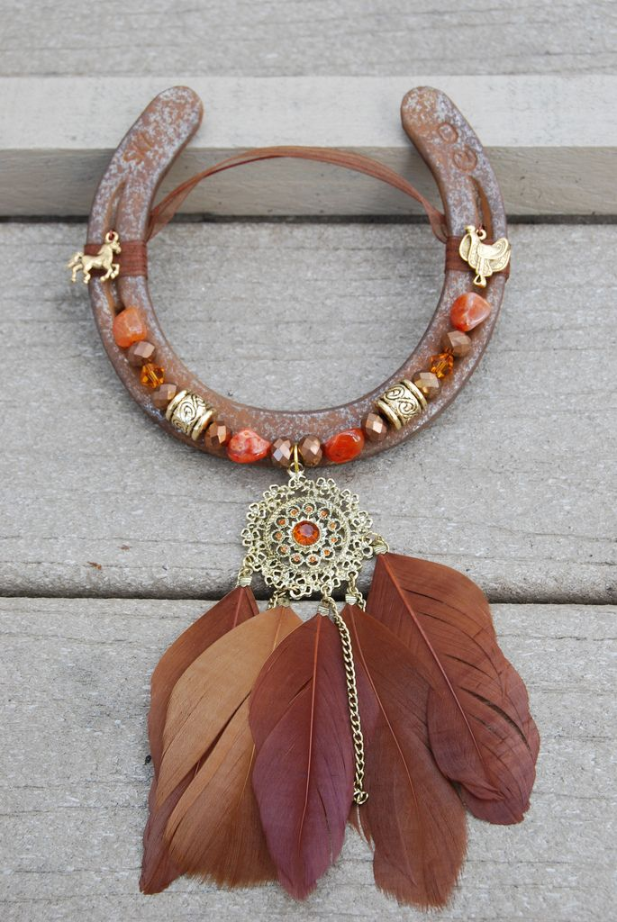 Rusted horseshoe with beautiful gold metal/orange crystal with 5 feather pendant. Gold plated horse and western saddle on the top. Orange and brown glass beads