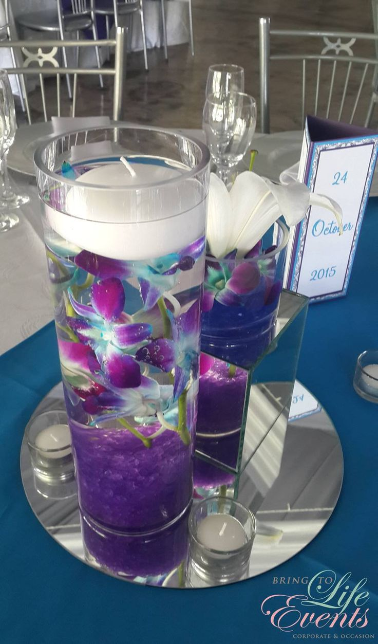 Gorgeous wedding with blue & purple colors. Orchids & lilies were used submerged in water.