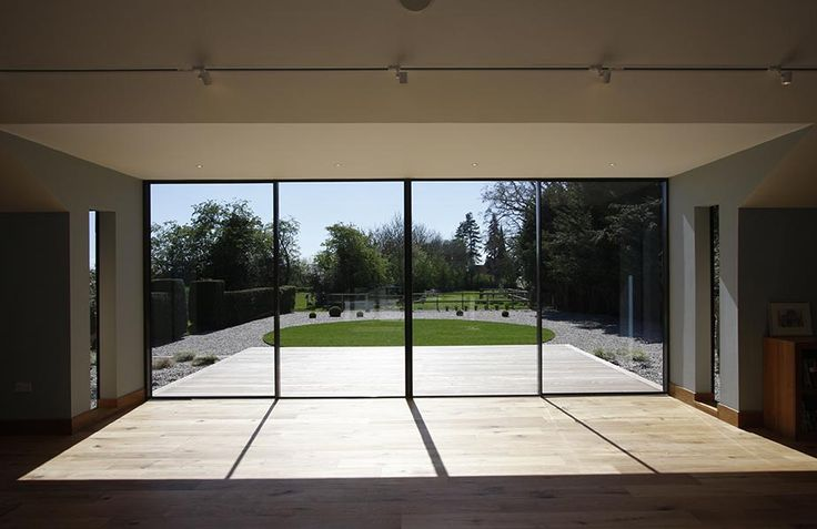 Thin framed sliding glass doors to the games room look over large gardens in Essex