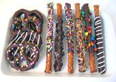 how to make chocolate dipped pretzels (use white chocolate / vanilla fudge & xmas colored sprinkles/toppings)