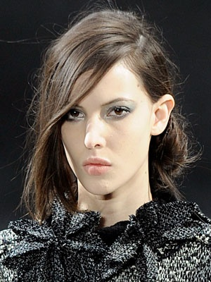 With a Side Chignon  At Chanel, hairstylist Sam McKnight also went for a boyish silhouette, pairing a romantic side chignon with an extreme side part and allowing long pieces of hair to fall into the models' faces. To get the look, McKnight suggests adding a texturizer, like Fekkai Coiff Bouffant Lifting and Texturizing Spray Gel, to give the hair hold. Then follow the steps he used backstage: Use a comb to create a deep side part, bring all your hair to one side at the back of your head (on…