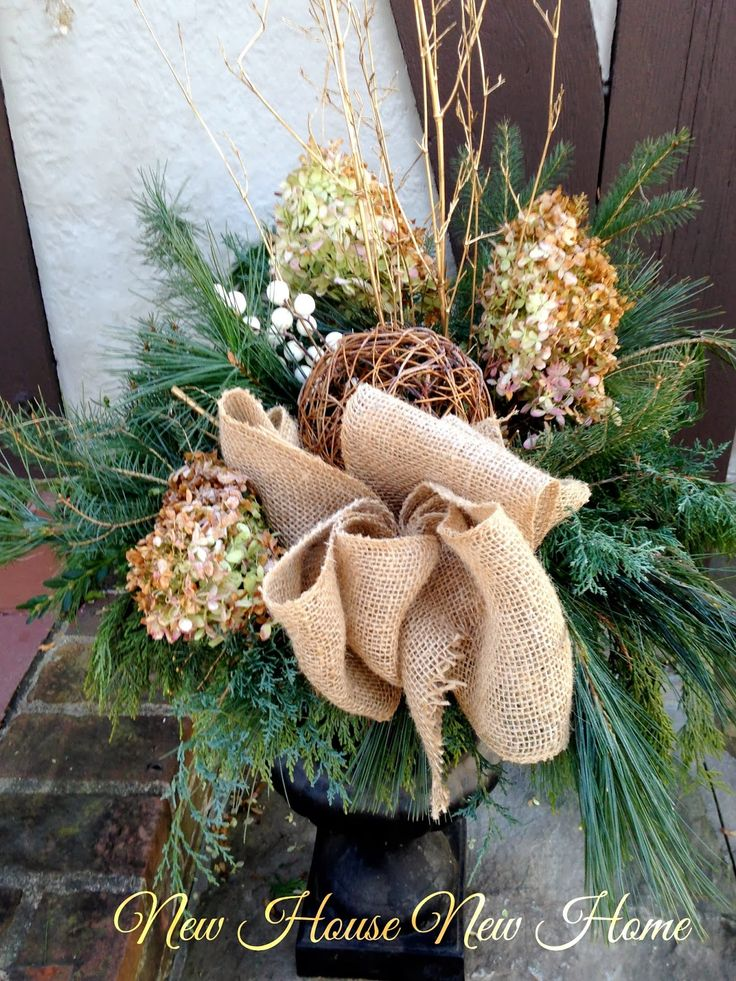 Our Christmas urns are inspired by a more casual, natural look with burlap, twigs and grapevine balls.