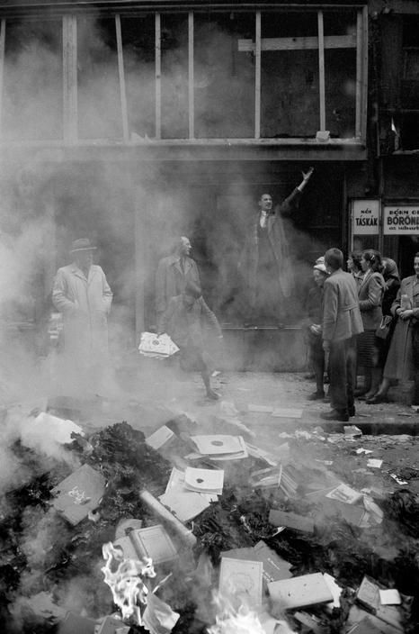 by ERICH LESSING - HUNGARIAN REVOLUTION 1956 --- Soviet bookshop is attacked by revolutionaries, books & portraits of hated communist leaders burnt in the street. An enthusiast recites poems by Sandor Petöfi, the poet of Hungarian uprising of 1848.