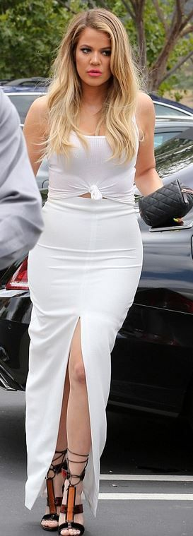 Who made  Khloe Kardashian's white split skirt, lace up brown sandals, and quilted black clutch handbag?