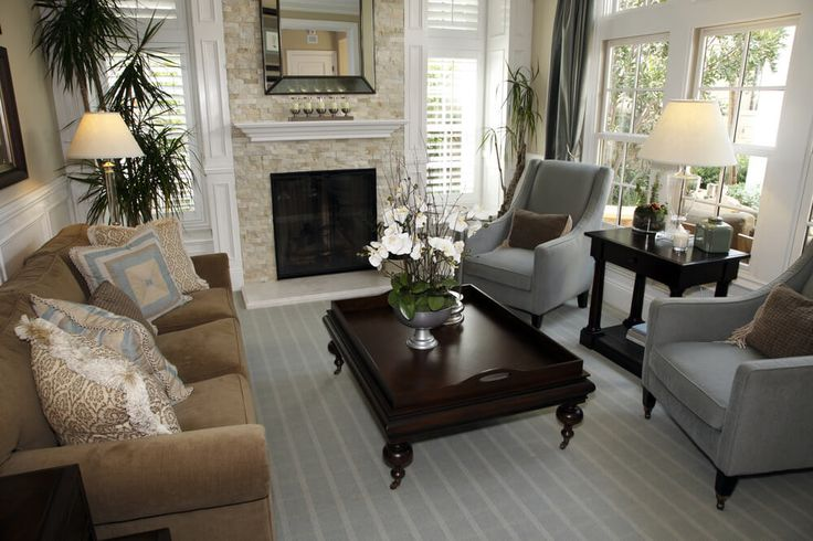 Traditional living room design with ornate dark wood coffee table, two blue-grey armchairs and one brown sofa. Two walls of the space have windows providing this living room with natural light.