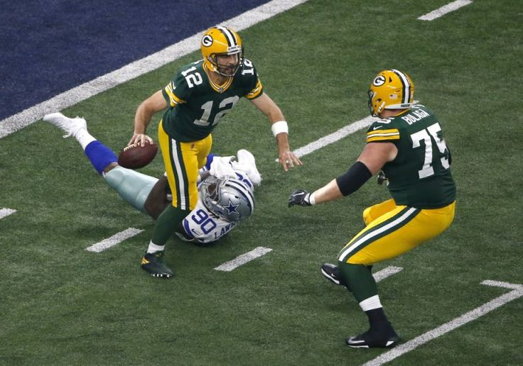 Green Bay Packers quarterback Aaron Rodgers (12) scrambles before throwing a pass as offensive tackle Bryan Bulaga watches Dallas Cowboys defensive end DeMarcus Lawrence (90) attempt the stop in the second half of an NFL football game, Sunday, Oct. 8, 2017, in Arlington, Texas. (AP Photo/Ron Jenkins)