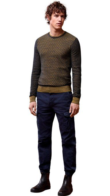 Male model wearing khaki sweater, blue trousers and black boots by BOSS Orange