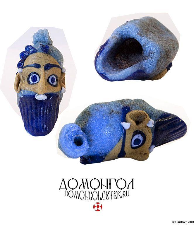 Подвеска из бирюзового стекла в технике накладного орнамента, изображающая лицо-маску.  Наиболее вероятная датировка - 4 век до н. э.
