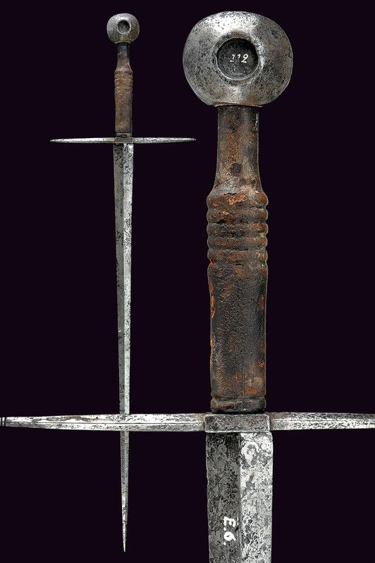 "Oakeshott Type XVa Medieval Sword circa 14th Century, Dating:	XIVth century  Description: Sharp blade of triangular profile with a diamond shape, old collection number ""E.6""; hilt with straight arms rising into the square section solid rectangular central ends with small buttons, big apple disc with circular cavities (old number inventory marked in white 112); original wooden handle covered with l  Read more…"