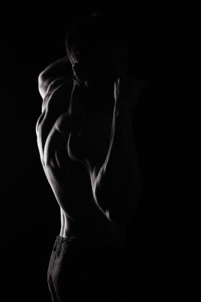 male fitness model bodybuilder back pose on black background
