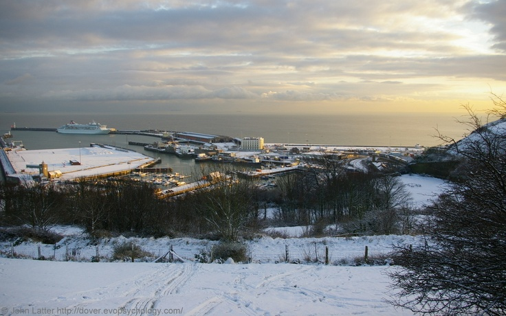 Dover Harbour and English Channel from the snow-covered Western Heights, Kent, England, UK. Western Docks: Fred Olsen Cruise Lines' Balmoral Cruise Ship, Admiralty Pier, and Jetfoil Basin. Prince of Wales Pier, Clock Tower, old Hoverport, Lord Warden House (ex-hotel, World War II Royal Navy HMS Wasp). Dover Marina: Tug Haven, Tidal Harbour, Crosswall Quay (Lifeboat Station), and Granville Dock. Winter 2009 Port of Dover Tourism, Travel, and Vacation. See…