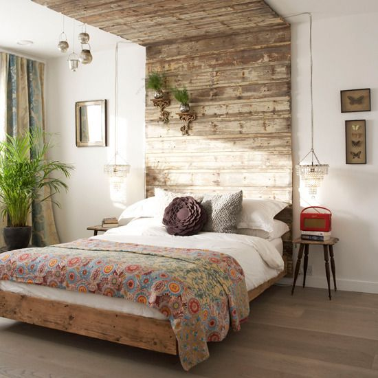 This textured headboard, which is made from reclaimed wood, is a stunning focal point for this rustic bedroom. To give it a decorative touch, add chandeliers and small gilt shelves to create a glamourous foil to the rough wood.