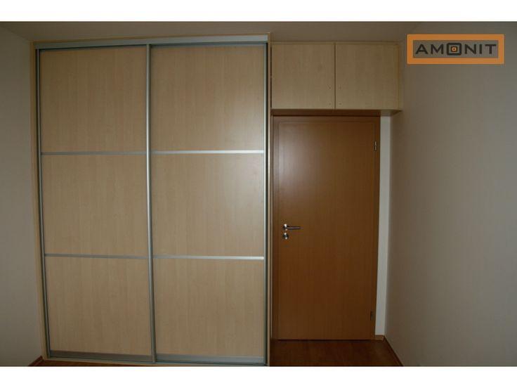 Nástavec nad dveřmi s pantovými dvířky doplňuje velkou skříň s posuvnými dveřmi