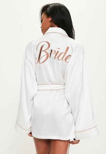 "Look sleek the night before your special day in this white satin robe with brown piping and ""bride"" embroidered on the back."
