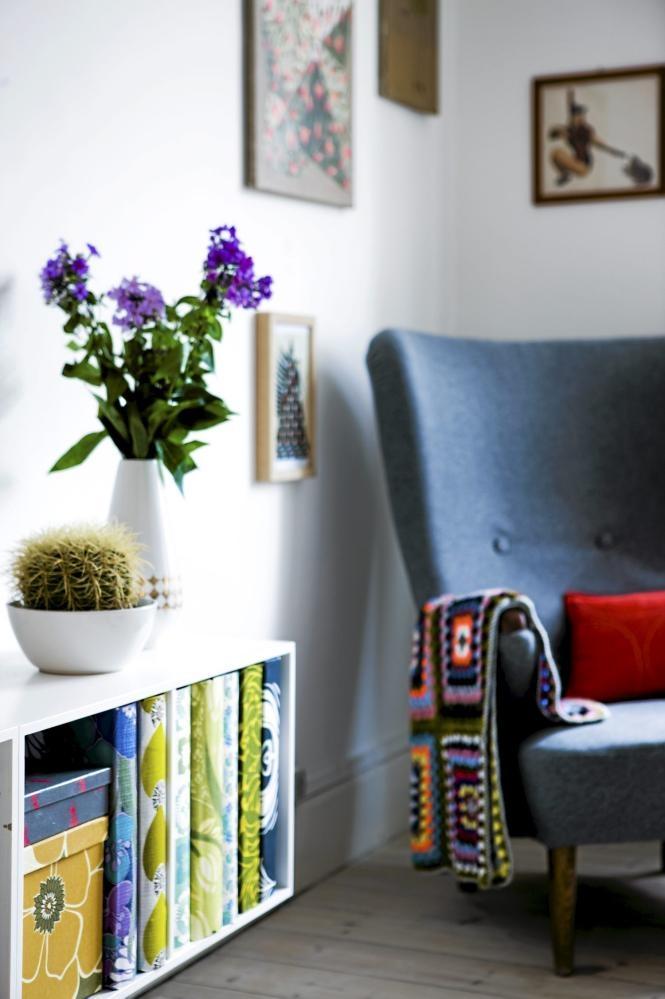Et heklet teppe, lenestolen og bildene på veggen er alle elementer fra retro-stilen. Også permene og eskene i hyllen har friske farger og mønster inspirert av 60- og 70-tallet.