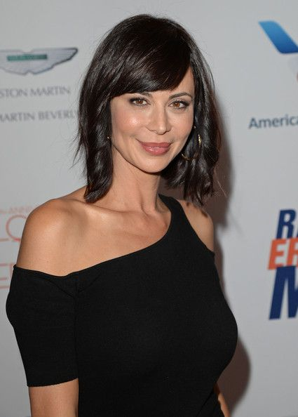 Catherine Bells chocolate hair looked super stylish with a wavy do and side swept bangs.