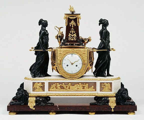 """Mantel Clock, French, Paris, about 1789.""""An ancient Roman religious rite inspired this clock, designed in the Neoclassical style after a drawing by Hubert Robert that was published as an engraving between 1771 and 1773. Two bronze priestesses of the temple of Vesta, the ancient Roman goddess of the hearth and its fire, carry the altar bearing the sacred flame."""""""