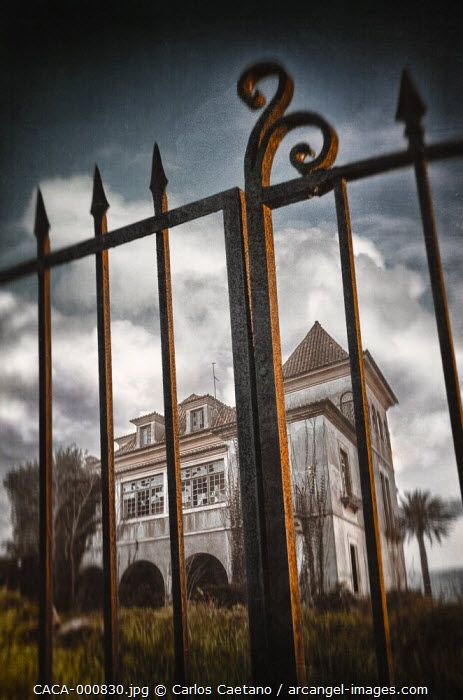 Detail of old iron gate to an abandoned haunted mansion