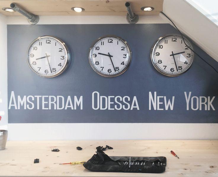 Leuke tekst muursticker met witte letters op een donker grijs structuur behang. Amsterdam, Odessa, New York, klokken muursticker, op maat gemaakt voor een klant door muurstickerstunter.nl