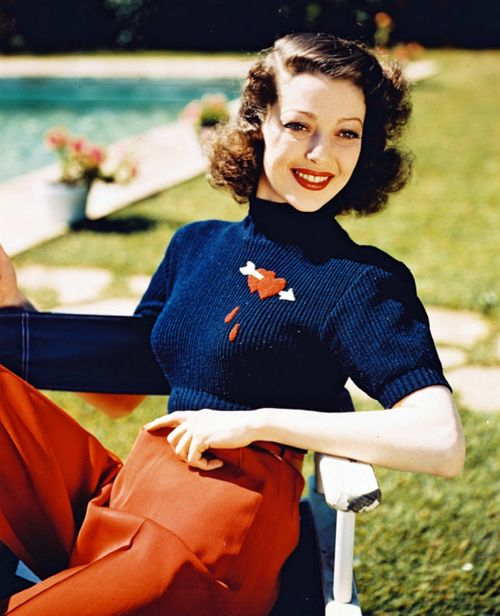 Loretta Young, 1930s fashion vintage fashion style color photo print ad movie star navy blue sweater heart arrow blood drops red trouser pants pool 40s