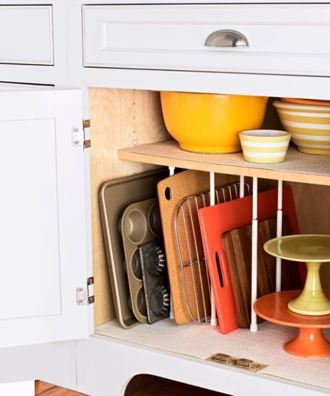 The first step to ending kitchen chaos: Store pots and pans near the stove and oven for easy access. Then, stow cookware according to function (colanders with pasta pots, mixing bowls with bakeware). Prevent flat items like cookie sheets and cutting boards from piling up, too, with tension curtain rods spaced between firmly installed shelves.