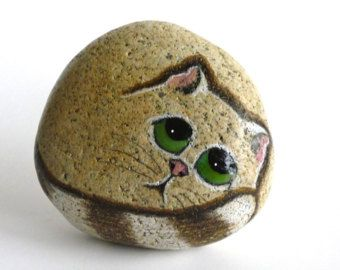 THE ONE THING I LOVE IS TO MAKE ARTWORK THAT MAKE PEOPLE SMILE.  Up for adoption is a hand painted Petrified Pet with green eyes. Dimensions: 4 1/2 X 3 X 3 1/2. Weight :1.8 lbs  I try to leave as much of the natural rock as possible. It makes it much more interesting when you can see the texture and color of the rock. This rock is Gray with black speckles.  I use a special technique to paint the eyes so they appear 3 dimensional. Because of this technique this cat does not like to l...