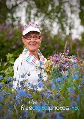 Healthy Elderly Smiling Woman With Flowers Stock Photo