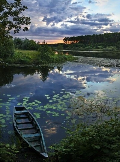 End of a lazy day in summer. Sit down by a boat and some still water and watch the sun go down.