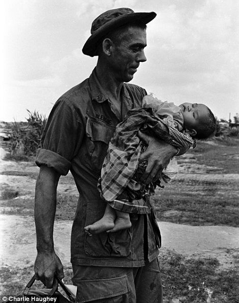 On tour of duty in the Vietnam War, Staff Sergeant Edgar D. Bledsoe of Olive Branch, Illinois cradles a critically ill child. Photo by Charlie Haughey.