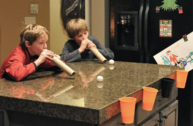 "Tape plastic cups to the edge of the table. Give each player a pile of ""snowballs"" (white ping pong balls) and an empty paper towel roll. Race to see how many snowballs each player can blow across the table and into the cup."