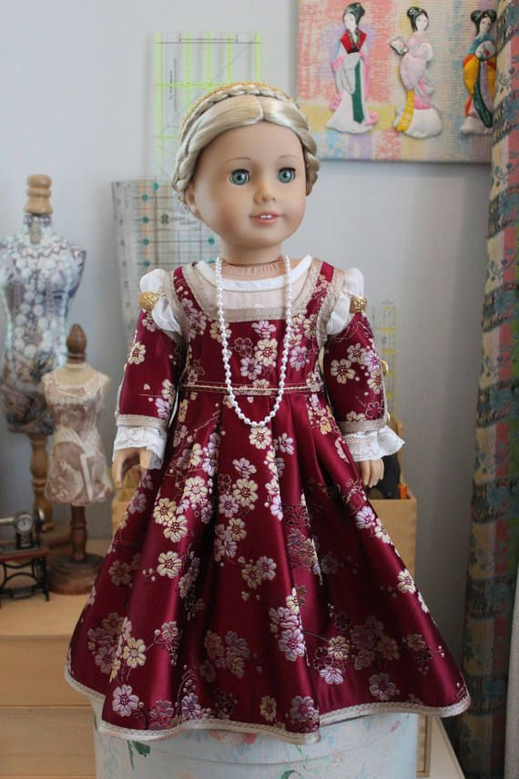 A Renaissance-style kirtle and underslip made for an 18 doll such as American Girl. The kirtle is made from a vintage floral silk brocade in wine with pink and gold details and all edges are finished in a modern gold shot silk. The sleeves, which have an edged opening down the center that closes with two (2) loops, in gold and white cording, and two (2) vintage goldtone buttons, are detachable -- there are two (2) loops on the kirtle which go over two (2) more vintage goldtone buttons at the…
