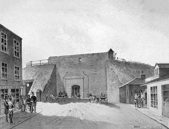 Première porte Saint-Jean (en place en 1850). Jusqu'à la fin des années 1840, l'éclairage des voies publiques était assuré par les aubergistes, taverniers et hôteliers qui devaient accrocher une lampe à huile à la porte de leur établissement. En 1847, la Quebec Gas Company est créée.: