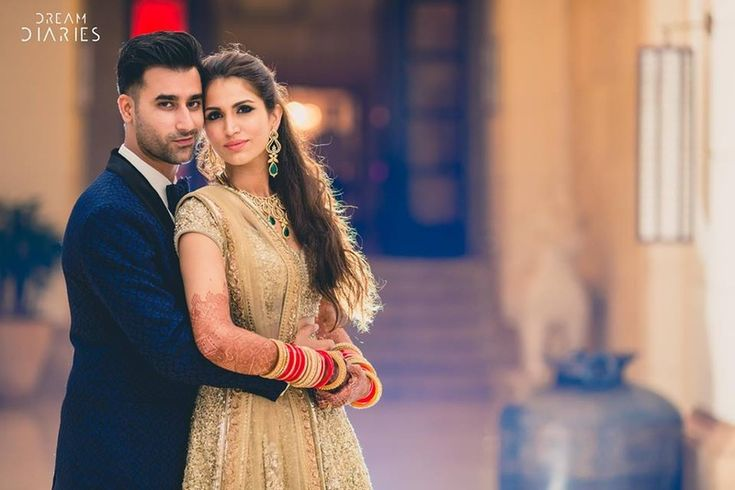 Navy blue textured suit and gold lehenga for the royal like reception ceremony held at Grand Hyatt, Goa. | weddingz.in | India's Largest Wedding company | Couple Portrait Photography | Indian Wedding Photography @dreamdiaries |