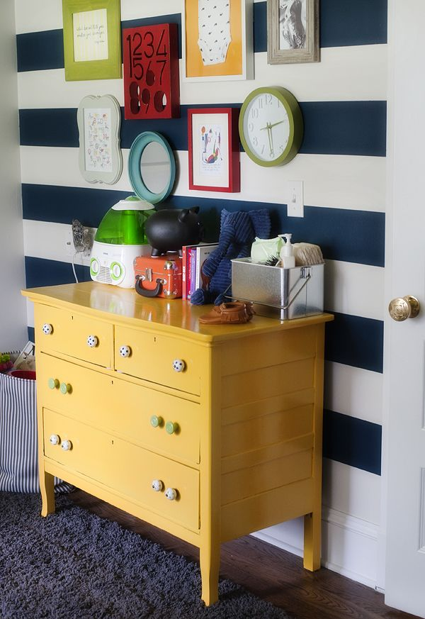 Bright Nursery, wall decor, clock, striped wall, navy, white, green, red, yellow, colorful frames, yellow dresser