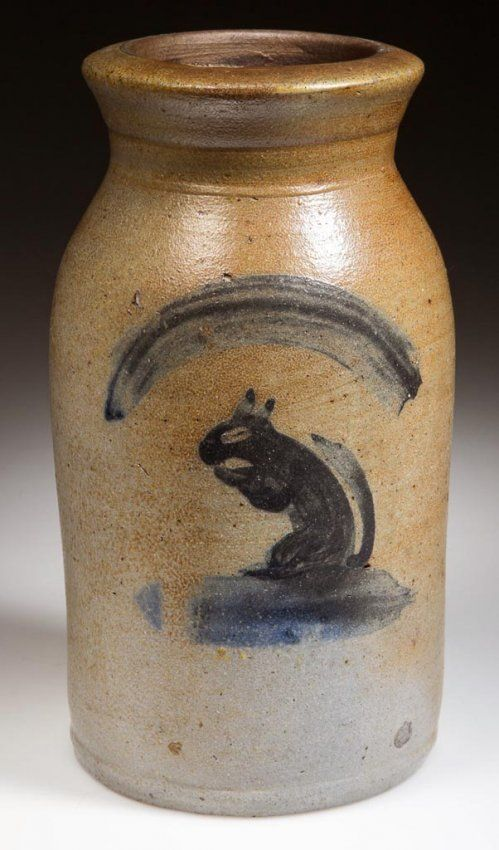 "Sold $42,500 FINE AND RARE THOMPSON POTTERY, MORGANTOWN, WEST VIRGINIA FOLK-ART-DECORATED STONEWARE DIMINUTIVE CANNING JAR, salt-glazed, approximately one-quart capacity, shouldered cylindrical form with a flared neck and nearly-flat rim. Albany-slip glazed interior. Brushed cobalt decoration of a seated squirrel eating a nut below an arch device. Attributed to the Thompson Pottery (active c. 1810-1890), Morgantown, WV. Circa 1860-1870. 7 3/4"" H, 3 1/2"" D rim.Literatu"