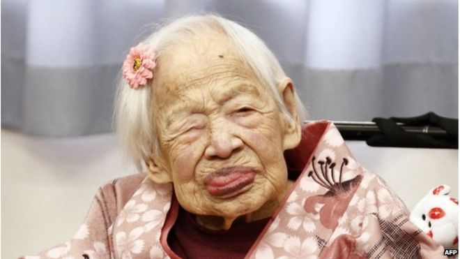 This picture taken on 4 March 2015 shows the world's oldest woman Misao Okawa (C) posing for a photo at her nursing home in Osaka, western Japan