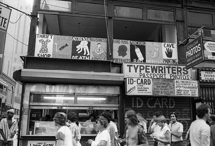 #Mousse61 #MousseMagazine Sidewalk view of COLAB's Times Square Show with signs by Tom Otterness advertising the attractions inside, New York, June 1980. Photo: © Lisa Kahane, NYC. All Rights Reserved