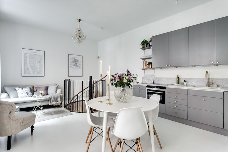 Kitchen, dining, living room of a small apartment in Scandinavian white/grey