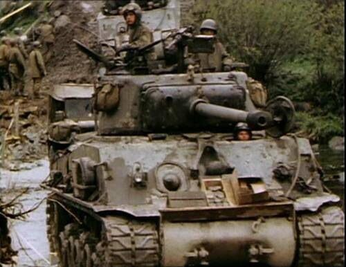 An American M4A3 (76mm) Sherman tank crosses the Muhl River in Austria. Spring, 1945. A Dodge weapons carrier follows it, just behind the truck, a M4A3E2 Sherman tank descends the embankment to enter the same river.