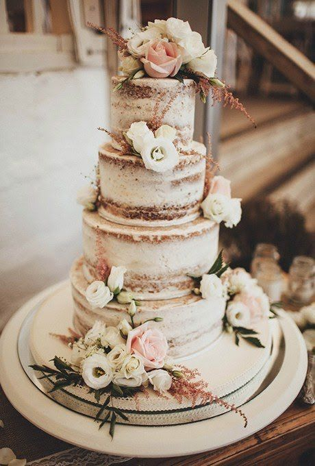 A nearly-naked rustic wedding cake by Sweet Thought Cakes with flowers and foliage.