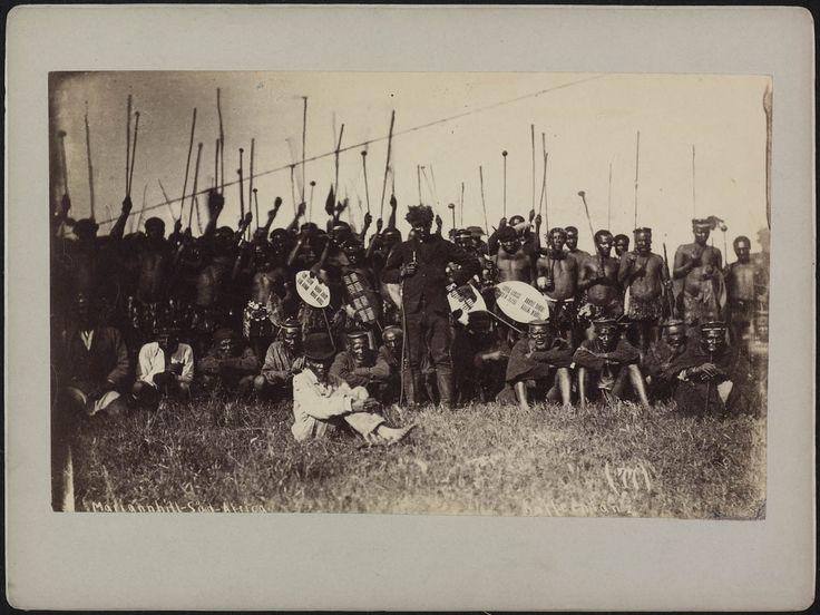 Groepsfoto van een stamhoofd met zijn soldaten, opgesteld voor het uitvoeren van de oorlogsdans ukuketa
