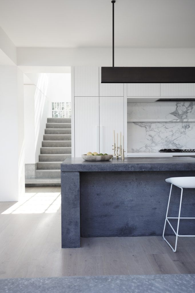 Kitchen: white panelled cabinets, marble splashback, concrete benchtop island with waterfall, pale timber floorboards, undermount rangehood, black linear pendant light, brass candle holder