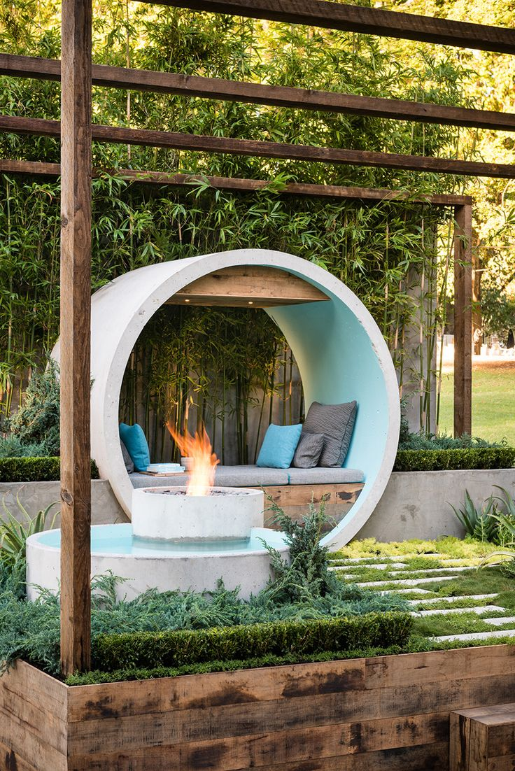 Using a number of concrete pipes, the designer has created a meditation moon gate / day bed, a reflective water feature, and a fire pit.