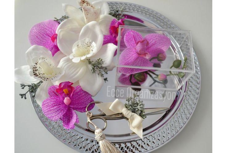 Metal oval tepsimizin kenarları kendinden örgülüdür, üstünde yapay beyaz ve mor orkidelerle süslenmiştir. Ürün set olarak hazırlanabilmektedir. Setimizin içerisinde şeffaf içini gösteren pleksiden oluşan yüzük kutumuz ve süslü makasımız da bulunmaktadır.