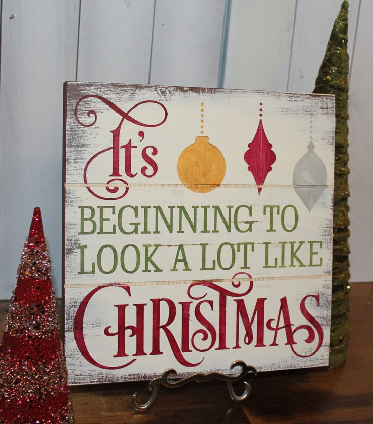 Beautiful Christmas decoration. Sign can be hung on the wall or put on shelf.....   Measures about 11.5x 11.5 x 3/4. apx  Pictured: Brown Board, Ivory base, with font in country green, wine red, gold and silver. Rustic Finish. This has been put on one of our faux plank boards   Comes with a key hole drilled in the back so it lays flat against the wall.  Most of our signs are made from re-claimed lumber. This means that there are imperfections in the wood. This adds to the character and…