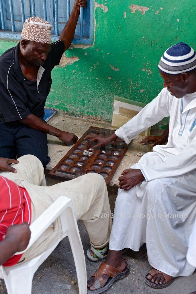 2 players challenge in Mancala, a typical African board game.